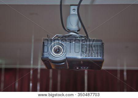 A White Overhead Projector On Ceiling Indoors. Modern Video Projector On Ceiling In Room . Black Pro