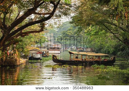 Beautiful backwaters landscape in Alleppey city with traditional houseboats at sunset in Kerala, India