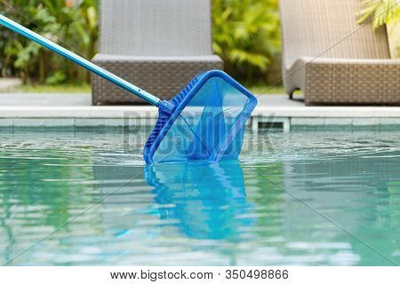 Cleaning Swimming Pool Of Fallen Leaves With Skimmer Net Equipment Against Sun Resort Loungers At Su