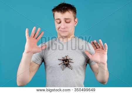 The Young Man Spreads His Arms To The Side And Looks With Hostility At The Spider That Sits On His C