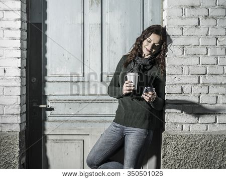 Young Woman With Red Hair Using Her Cellphone And Drinking Coffee From A Takeout Cup.