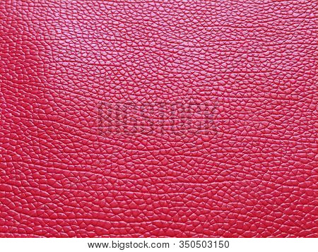 Faux Red Leather. Separate Grooves And Elevations On The Surface Of A Bag Or Shoe. Reflection Of The