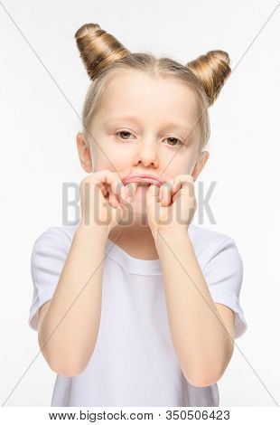 Little Girl Made A Sad Grimace On A White Background. The Concept Of Manifestation Of Discontent Or