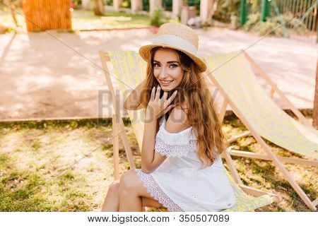 Attractive Happy Girl In Vintage Lace Dress Playing With Her Hair Chilling In Chaise-longue Under Th