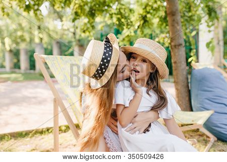 Pretty Lady Sitting In Chaise-longue And Holding Daughter On Knees, Enjoying Good Summer Day. Outdoo