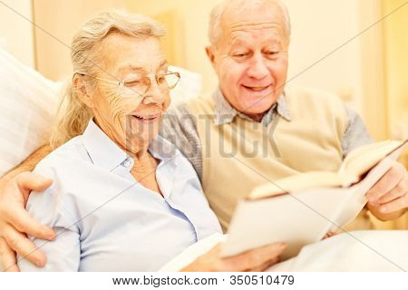Happy senior couple reading a book together in senior citizen residence