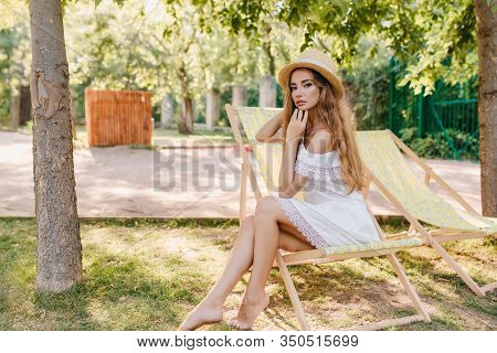 Graceful Barefooted Lady In Straw Hat Sitting On Chaise-longue With Pensive Face Expression. Outdoor