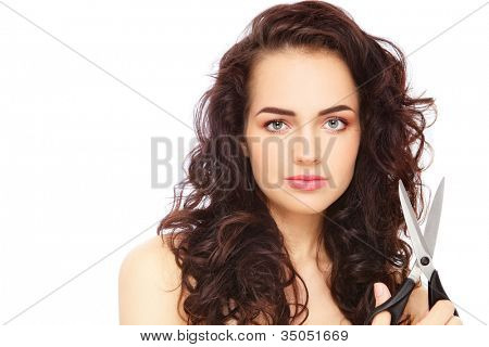 Young beautiful woman with long curly hair and scissors in her hand, on white background