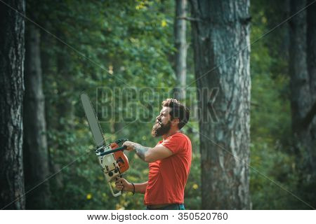 Lumberjack In The Woods With Chainsaw Axe. Firewood As A Renewable Energy Source. Stylish Young Man