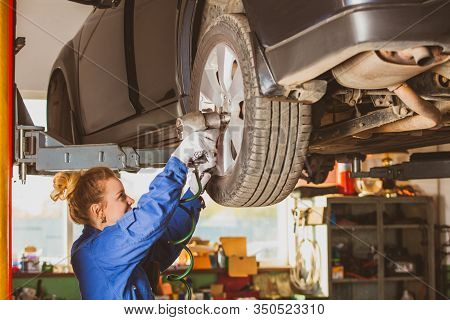 Female Tyre Service Worker Fixing Wheels On Lifted Car