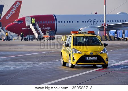 Krakow, Poland 20.12.2019: Yellow Toyota Yaris Airport Technical Service Car Is Driving Along The Ru