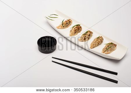 Delicious Gyoza On Plate Near Chopsticks And Soy Sauce On White Background