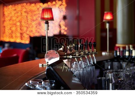 Bar counter with beer taps, glasses and bottles. Interior of pub, nightclub, cafe or restaurant