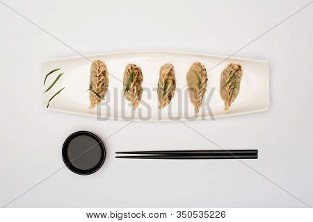 Top View Of Delicious Gyoza On Plate Near Chopsticks And Soy Sauce On White Background