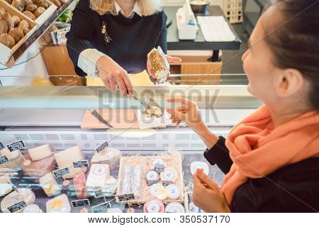 Customer and shop clerk at the cheese counter of supermarket testing cheese