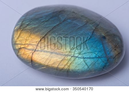 Green Blue And Yellow Rounded Labradorite Crystal Stone Isolated On Light Background