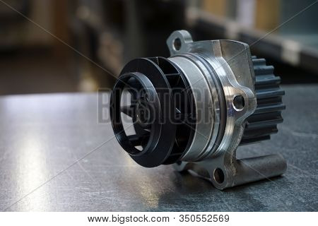 Engine Parts Of A Modern Car. Cooling System. New Original Quality Cooling Pump On A Steel Backgroun