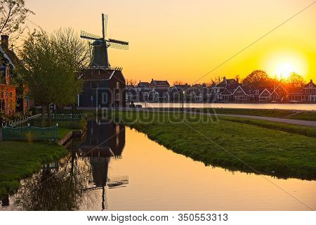 Old Dutch Windmill By A River Zaan In Setting Sun With Reflection In A Canal