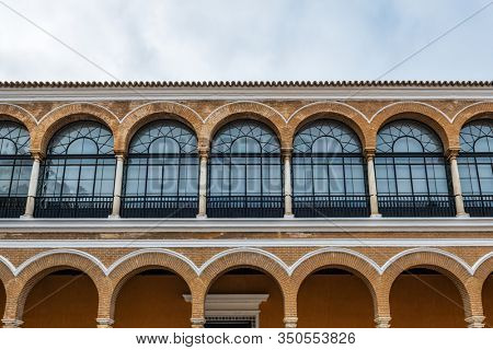 SEVILLE, SPAIN - December 09 2019: Row of arched windows in Patio de la Monteria courtyard exterior facade in Real Alcazar Royal residence in Seville, Spain