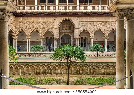 SEVILLE, SPAIN - December 09 2019: Patio de las Doncellas courtyard, Real Alcazar, Seville Spain viewed between columns, a Unesco World Heritage Site