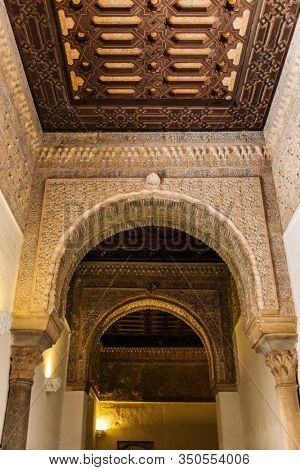 SEVILLE, SPAIN - December 09 2019: Ornamented arches and ceiling of the corridor inside the Royal Alcazars of Seville castle in Spain. Famous Andalusian architecture