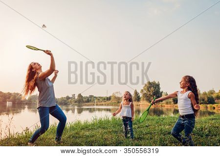 Mothers Day. Woman Playing Badminton And Having Fun With Daughters In Summer Park. Family Time