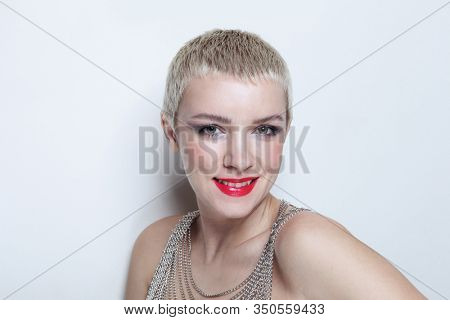 Vintage style portrait of young smiling woman with short blonde hair and fancy makeup