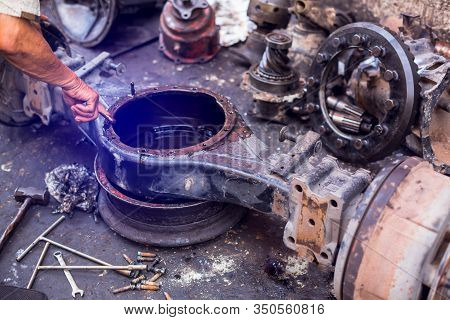 The Mechanic Is Fixing The Old Rear Gear Of The Car. Old Machine Parts In Warehouses.