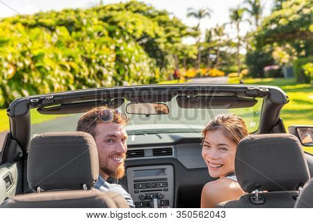 Happy road trip couple having fun driving luxury sports convertible car rental on travel vacation summer holidays looking back smiling. Interracial people tourists Asian woman, Caucasian man friends.