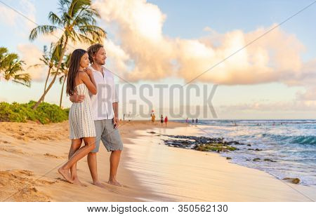Couple on romantic sunset beach walk relaxing during Hawaii summer travel vacation on Kauai island, USA. Asian woman in white dress, Man in linen shirt.