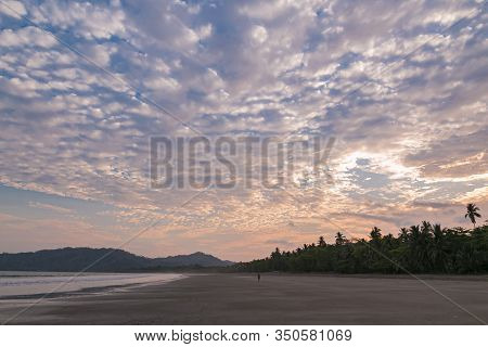 Person Walking On The Sand During A Sunset At Tambor Beach, Puntarenas Costa Rica