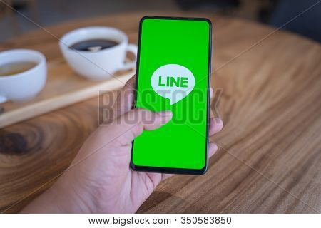 Chiang Mai, Thailand - Jan.18,2020: Man Holding Xiaomi Mi Mix 3 With Line Apps On Screen On Wooden D