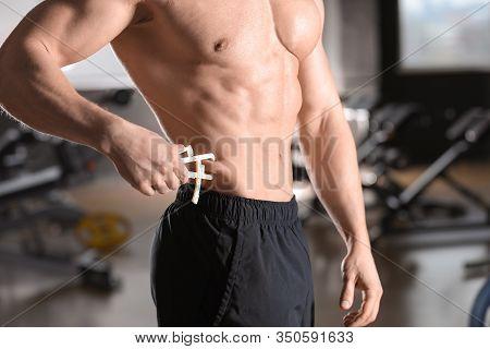 Man Measuring Body Fat Layer With Caliper Indoors, Closeup