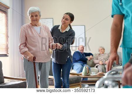 Care Worker Helping To Elderly Woman With Stick In Geriatric Hospice