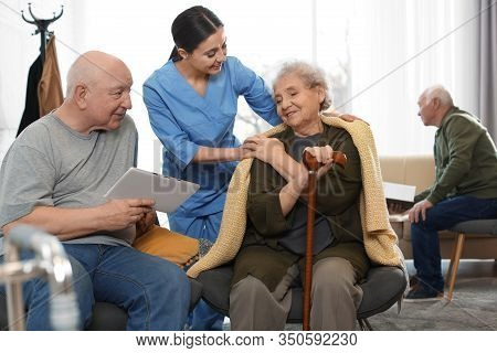 Nurse Taking Care Of Elderly Patients In Geriatric Hospice