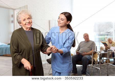 Nurse Taking Care Of Elderly Woman In Geriatric Hospice