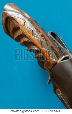 Wooden Hilt Of An Old Hunting Knife On A Blue Background.   The Knife Is Hidden In Black Leather Sca