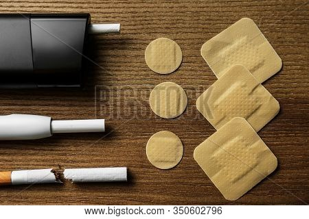 Flat Lay Composition With Nicotine Patches And Cigarettes On Wooden Table