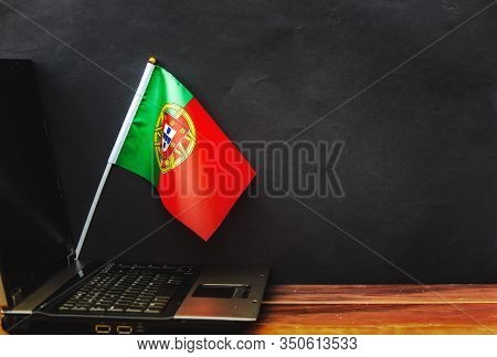 Flag Of Portugal , Computer, Laptop On Table And Dark Background
