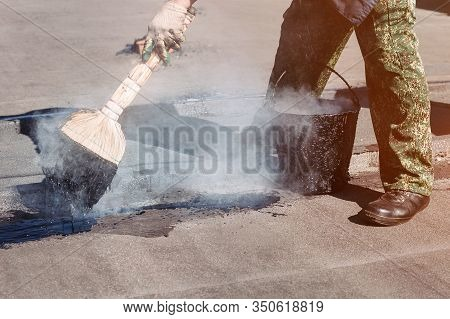 Worker Repairs The Roof With Molten Tar From A Bucket With A Broom. Roof Repair Tar.