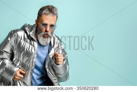 Gray-haired, Bearded, Mature Man In Purple Pullover And Sunglasses, Silver Colored Down Jacket, Jean