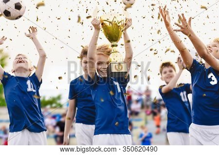 Champion Youth Soccer Team With Winning Trophy. Boys Football Team Celebrating Victory In School Com