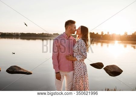 Loving Couple Kissing On The Lake At Sunset. Beautiful Young Couple In Love Walking On The Shore Of