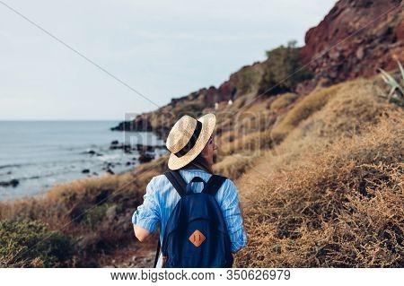 Woman Traveler Walking On Beach In Akrotiri, Santorini Island, Greece By Aegean Sea. Tourism, Travel