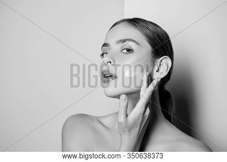 Portrait Of Beautiful Young Lady Touching Cheek With Hand Applying Face Cream. Selfcare Routine And
