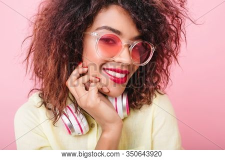 Joyful African Female Model With Red Lips Smiling To Camera, Touching Her Face. Close-up Portrait Of