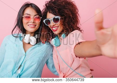 Excited African Girl With Red Manicure Making Selfie With Hispanic Female Friend. Fashionable Latin