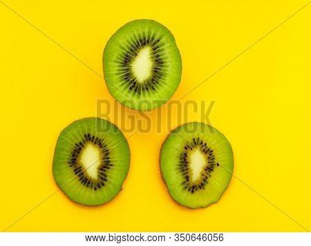 Three Circles Of Kiwi On A Yellow Background. Kiwi Cutaway