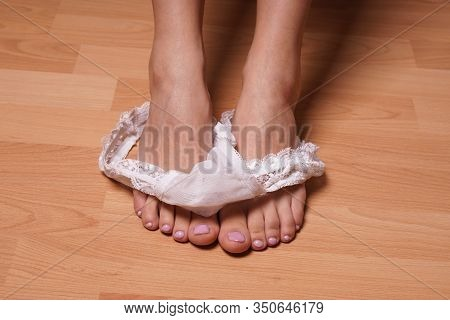Close-up Feet Of Unrecognizable Young Woman Undressing Dropping White Thong Panties On Bedroom Floor