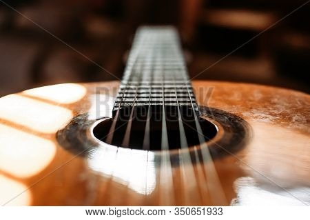 Close Up Of Classical Guitar Head With Sound Hole And Stings. Blurred Background